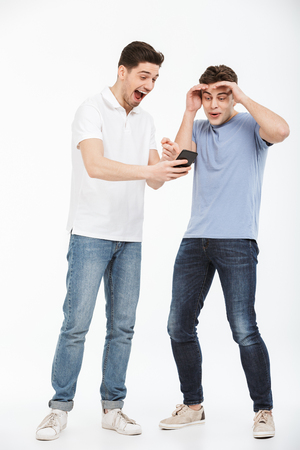 Full length portrait of two surprised young men looking at mobile phone isolated over white background
