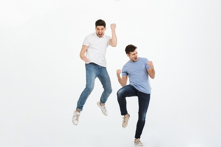 Full length portrait of two happy young men jumping and celebrating success isolated over white background