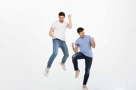 Volledig lengteportret van twee gelukkige jonge mensen die en succes springen vieren dat over witte achtergrond wordt geïsoleerd