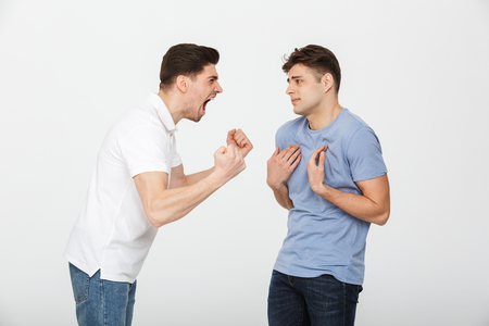 Full length portrait of two frustrated young men arguing isolated over white background Stock Photo
