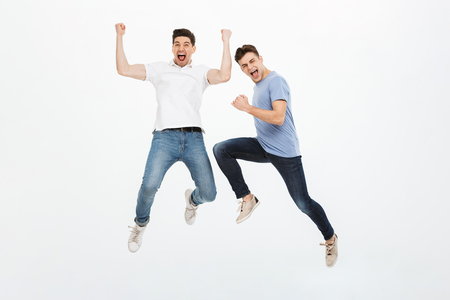 Full length portrait of two excited young men jumping and celebrating success isolated over white background