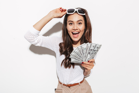 Portrait of a cheerful young asian businesswoman in sunglasses showing money banknotes and celebrating isolated over white background