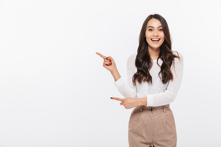 白い背景に隔離されたコピースペースに指を向ける幸せなアジアのビジネスウーマンの肖像