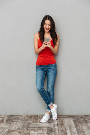 Full length image of Happy brunette woman in casual clothes writing message on smartphone over grey background