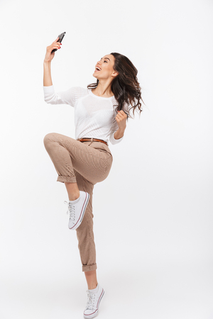 Full length portrait of an excited asian businesswoman celebrating with mobile phone isolated over white background