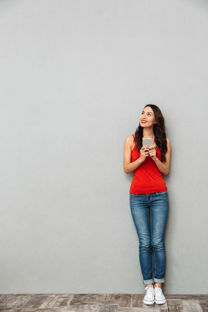Full length image of Pensive smiling brunette woman in casual clothes holding smartphone and looking up over grey background Foto de archivo