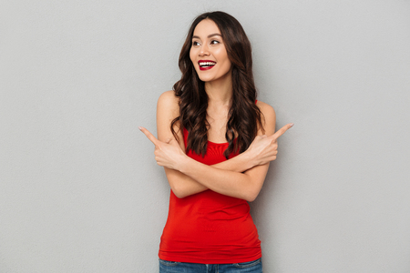 Happy brunette woman in casual clothes with crossed arms pointing to the sides while looking away over grey background