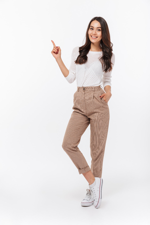 Full length portrait of a smiling asian businesswoman pointing finger away isolated over white background Foto de archivo