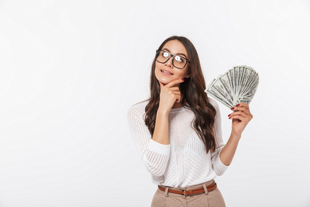 Portrait of a pensive asian businesswoman showing money banknotes isolated over white background