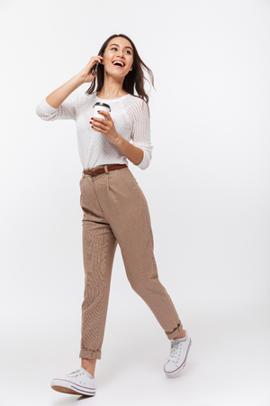 Portrait of a cheerful asian businesswoman talking on mobile phone while holding cup of coffee to go and walking isolated over white background