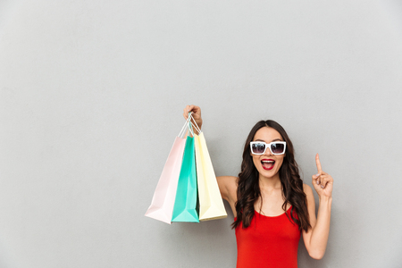Happy brunette woman in casual clothes and sunglasses holding packages and having idea while looking at the camera over grey background