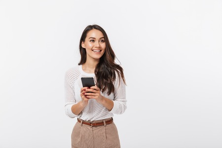 Portrait of a happy asian businesswoman holding mobile phone and looking away isolated over white background Imagens
