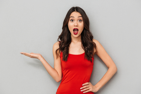 Image of shocked young asian woman standing isolated over grey wall background looking camera showing copyspace. Stock fotó
