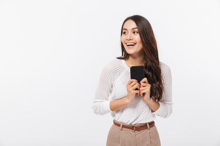 Ritratto di una donna d'affari asiatica felice utilizzando il telefono cellulare e guardando lontano isolato su sfondo bianco
