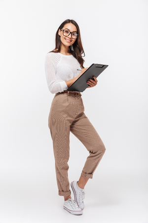 Full length portrait of a happy asian businesswoman holding clipboard isolated over white background