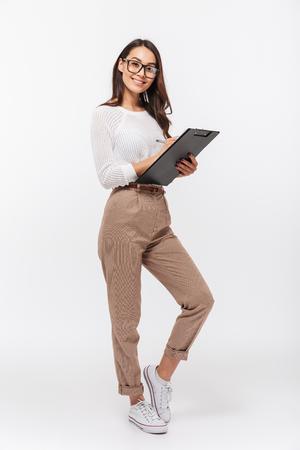 Retrato de cuerpo entero de una feliz empresaria asiática sosteniendo el portapapeles aislado sobre fondo blanco.