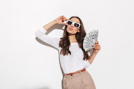 Portrait of a confident young asian businesswoman in sunglasses showing money banknotes and celebrating isolated over white background