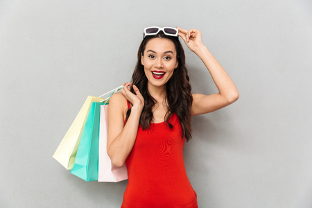 Surprised happy brunette woman in casual clothes takes off sunglasses while looking at the camera with packages over grey background Stock Photo