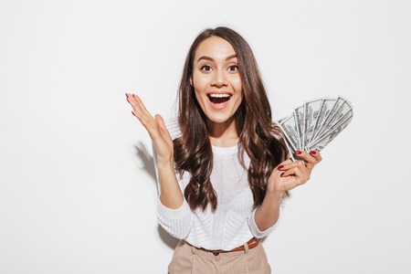 Portrait of an excited young asian businesswoman showing money banknotes and celebrating isolated over white background 写真素材 - 101486727
