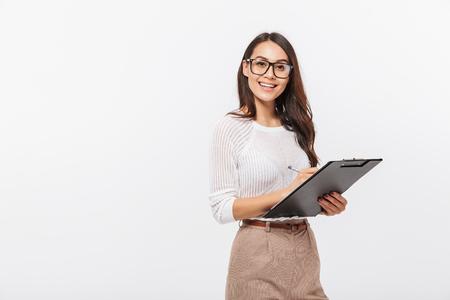 Ritratto di una felice imprenditrice asiatica tenendo appunti isolato su sfondo bianco