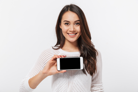 Ritratto di una donna d'affari asiatica sorridente che mostra il telefono cellulare dello schermo in bianco isolato sopra priorità bassa bianca Archivio Fotografico