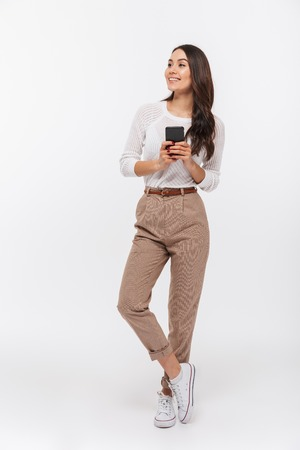 Full length portrait of a happy asian businesswoman using mobile phone and looking away isolated over white background