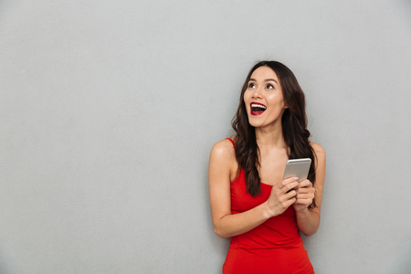 Cheerful brunette woman in casual clothes holding smartphone and looking away over grey background