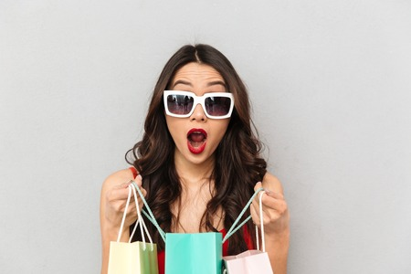 Shocked brunette woman in casual clothes and sunglasses opening packages and looking at the camera with open mouth over grey background 写真素材