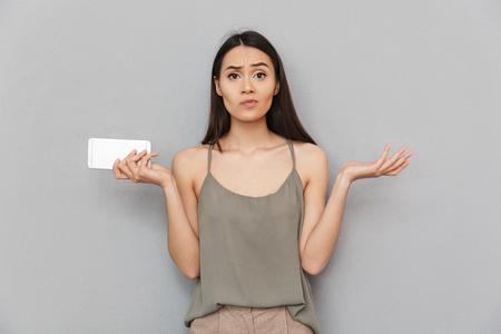 Retrato de una mujer asiática confundida sosteniendo teléfono móvil y encogiéndose de hombros aislado sobre fondo gris Foto de archivo