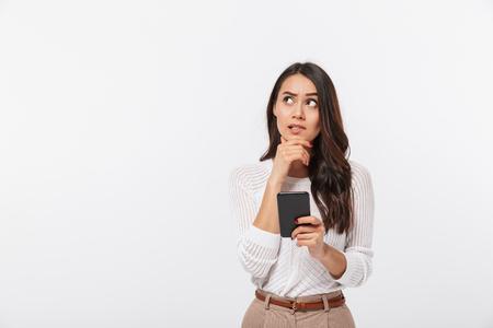 Porträt einer nachdenklichen asiatischen Geschäftsfrau, die Handy verwendet und weg lokalisiert über weißem Hintergrund schaut