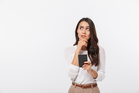 Portret van een peinzende Aziatische onderneemster die mobiele telefoon met behulp van en weg kijkt die over witte achtergrond wordt geïsoleerd