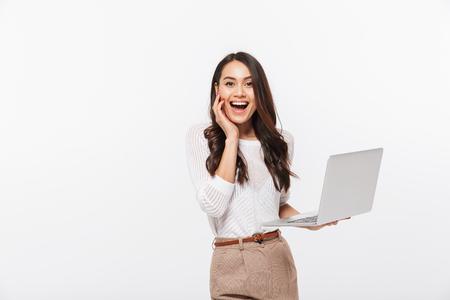 Retrato de una empresaria asiática emocionada sosteniendo ordenador portátil aislado sobre fondo blanco. Foto de archivo