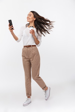Portrait of a cheerful asian businesswoman using mobile phone while holding cup of coffee to go isolated over white background
