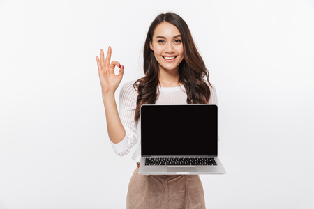 Portrait of a smiling asian businesswoman holding blank screen laptop computer and showing ok isolated over white background