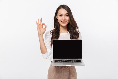 Ritratto di una donna di affari asiatica sorridente che tiene computer portatile dello schermo in bianco e che mostra ok isolato sopra priorità bassa bianca Archivio Fotografico
