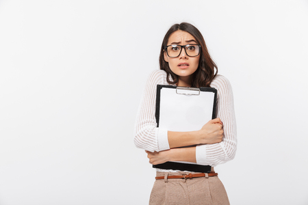 Portrait of a confused asian businesswoman holding blank clipboard isolated over white background