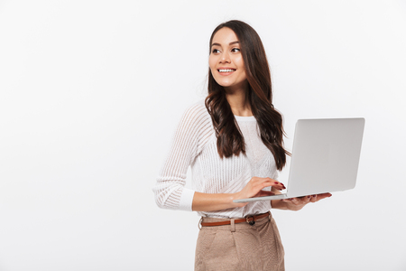 Portrait of a happy asian businesswoman holding laptop computer iand looking away solated over white background