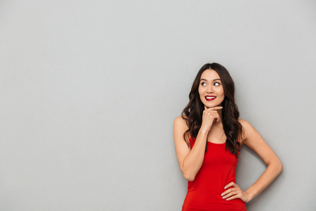 Image of cute thinking young asian woman standing isolated over grey wall background looking aside.