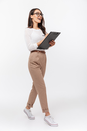 Full length portrait of a happy asian businesswoman holding clipboard while walking isolated over white background