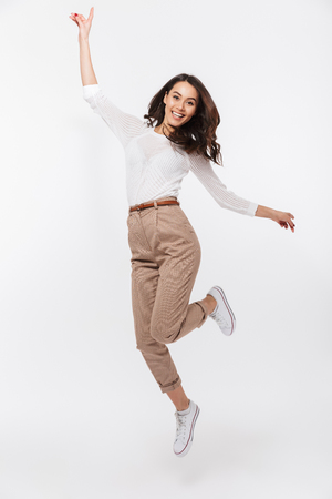 Full length portrait of a smiling asian businesswoman celebrating success isolated over white background