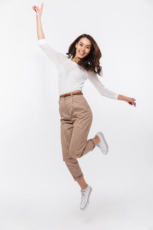 Porträt in voller Länge einer lächelnden asiatischen Geschäftsfrau, die Erfolg lokalisiert über weißem Hintergrund feiert Standard-Bild