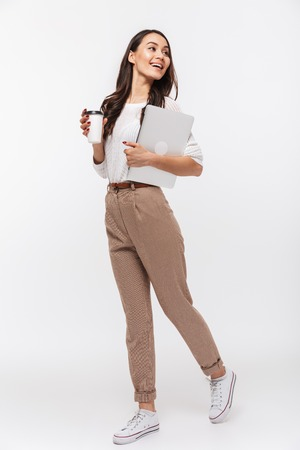 Full length portrait of a happy asian businesswoman carrying laptop computer and cup of coffee to go while walking isolated over white background
