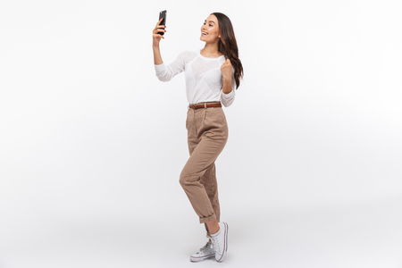 Full length portrait of a smiling asian businesswoman taking selfie with mobile phone isolated over white background