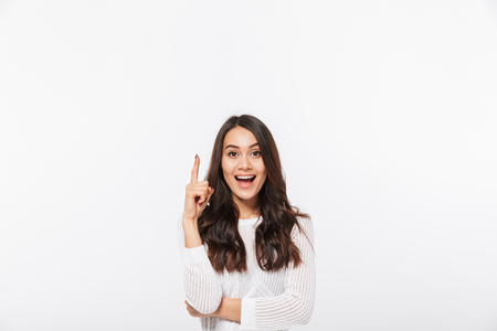 Portrait of a happy asian businesswoman pointing finger up at copy space isolated over white background