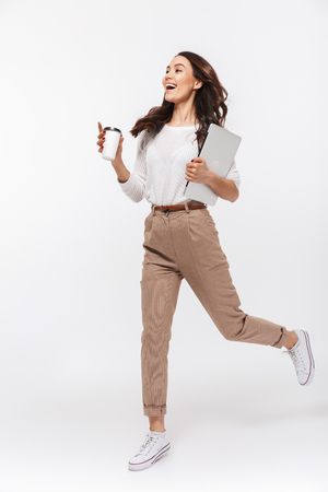 Full length portrait of a happy asian businesswoman carrying laptop computer and cup of coffee to go while running isolated over white background