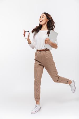 Portrait d'une femme d'affaires asiatique heureuse transportant un ordinateur portable et une tasse de café pour aller en cours d'exécution isolé sur fond blanc Banque d'images