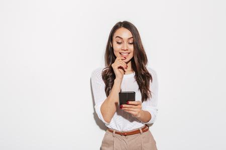 Porträt einer lächelnden asiatischen Geschäftsfrau unter Verwendung des Mobiltelefons lokalisiert über weißem Hintergrund Standard-Bild