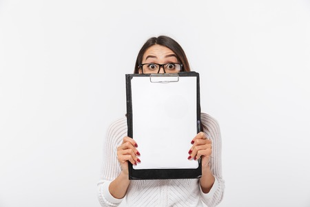Portrait of a confused asian businesswoman holding blank clipboard at her face isolated over white background