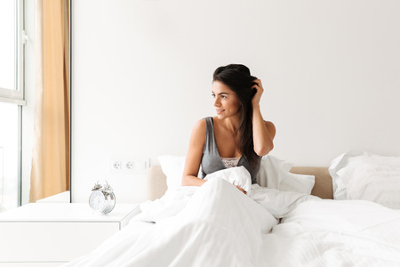 Portrait of relaxed young woman resting in bed after sleep with white clean linen at bedroom and looking in window