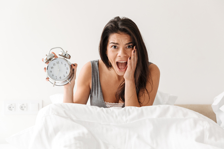 Image of shocked woman waking up and being late holding ringing alarm clock in panic